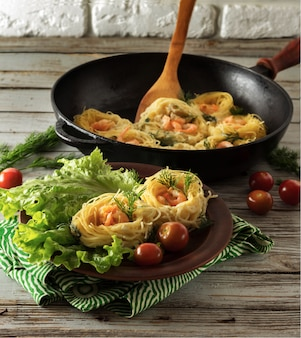 Pasta mit garnelen in form von nestern. eine portion nudeln auf einem teller mit salat. in der nähe von pfanne mit nudeln, tomaten und dill