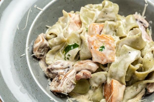 Pasta mit hühnchen-sahne-pilz-sauce. tagliatelle-nudeln. traditionelle italienische küche. hintergrund für lebensmittelrezepte. nahansicht.