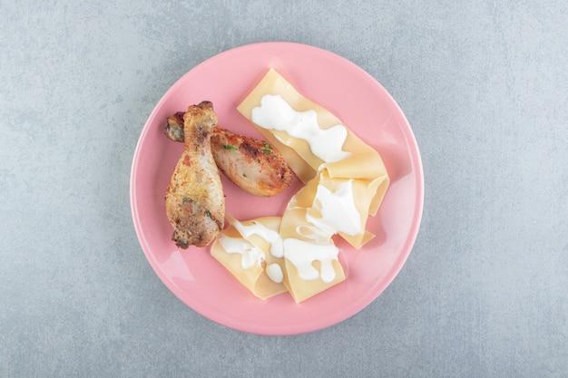 Pasta mit joghurt und hühnerbein auf rosa teller.