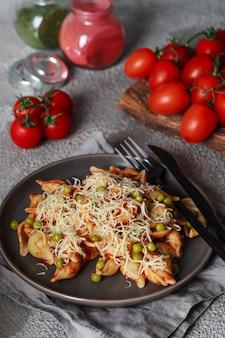 Pasta mit kirschtomaten, erbsen und parmesan. hausgemachte italienische pasta mit tomaten und sauce