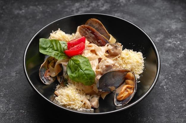 Pasta mit meeresfrüchten, muscheln, jakobsmuschel, rapana und käse auf einem schwarzen teller