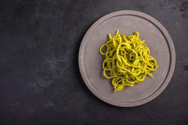 Pasta mit pesto, serviert auf grauer keramikplatte auf dunklem strukturiertem hintergrund, selektiver fokus, draufsicht, kopierraum