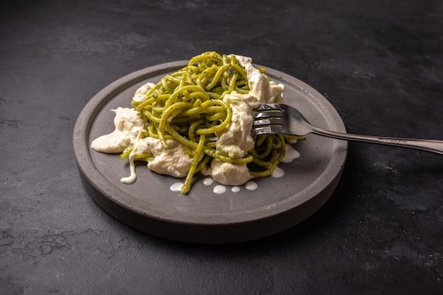 Pasta mit pesto und stracatella, serviert auf grauer keramikplatte und gabel auf dunklem strukturiertem hintergrund, selektiver fokus, draufsicht