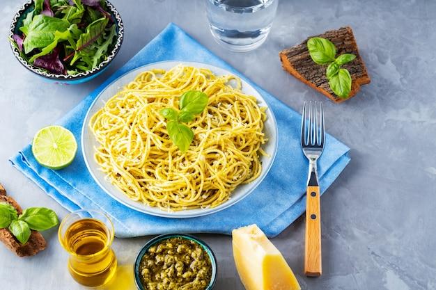 Pasta mit sauce pesto und salat von grüns mischen. spaghetti mit pesto-sauce und frischem basilikum auf grauem hintergrund. ansicht von oben