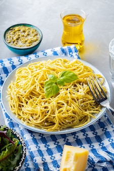 Pasta mit sauce pesto und zutaten. spaghetti mit pesto-sauce und basilikum auf grauem hintergrund. traditionelle italienische küche. foodstyling