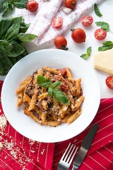Pasta mit tomaten, parmesan und basilikum. in einem weißen teller