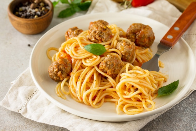 Pasta nach italienischer art spaghetti mit fleischbällchen mit tomatensauce auf stein- oder betontisch