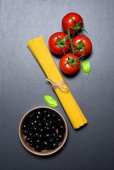 Pasta oder italienische spaghetti, tomaten, oliven und oregano auf schwarzem stein schiefer hintergrund