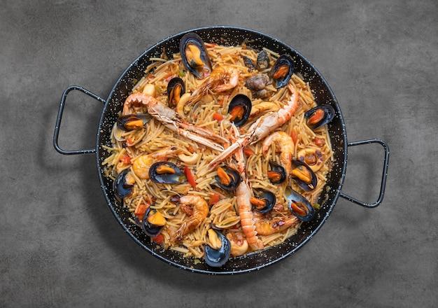 Pasta paella mit meeresfrüchten, spanische küche auf rustikalem tisch