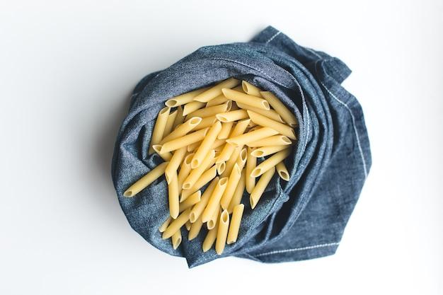 Pasta penne in einem blauen leinen