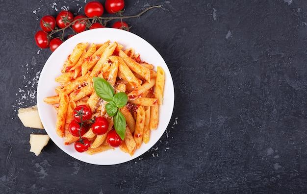 Pasta penne mit tomatensauce, frischem basilikum, gerösteten tomaten und parmesan
