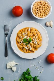 Pasta pipa das rigat mit einer sauce aus kichererbsen und tomaten, bestreut mit feta und koriander