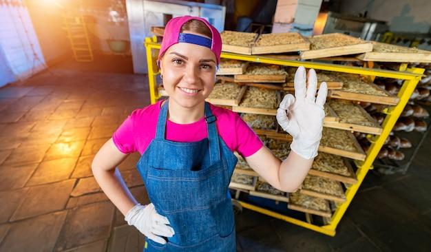 Pasta-produktion im werk. holzkisten mit nudeln in bäckerhänden. frau mit ok-zeichen. industrielle arbeit der technologischen produktionsfabrik, rohe makkaroni-nahaufnahme.