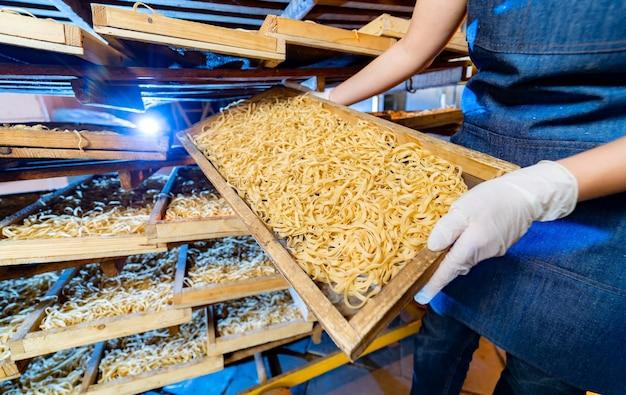 Pasta-produktion im werk. holzkisten mit nudeln in bäckerhänden. industrielle arbeit der technologischen produktionsfabrik, rohe makkaroni-nahaufnahme.
