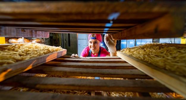 Pasta-produktion im werk. holzkisten zum ausruhen von makkaroni. industrielle arbeit der technologischen produktionsfabrik, rohe makkaroni-nahaufnahme.