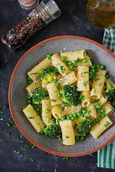 Pasta rigatoni mit brokkoli und erbsen. veganes menü. diätetisches essen. flach liegen. draufsicht.