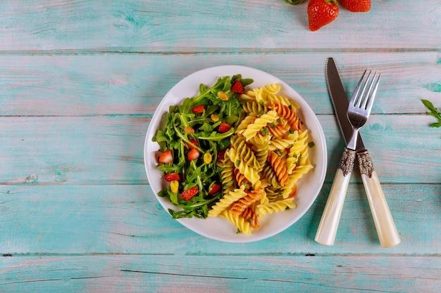 Pasta rotini mit rucola-erdbeersalat mit gabel und messer auf holzoberfläche draufsicht