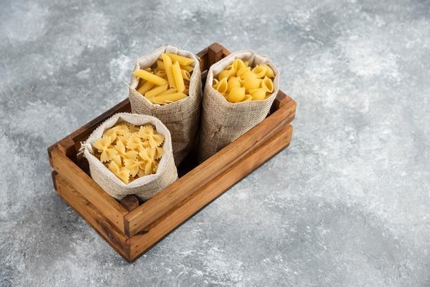 Pasta-sorten im rustikalen korb in einem holztablett.