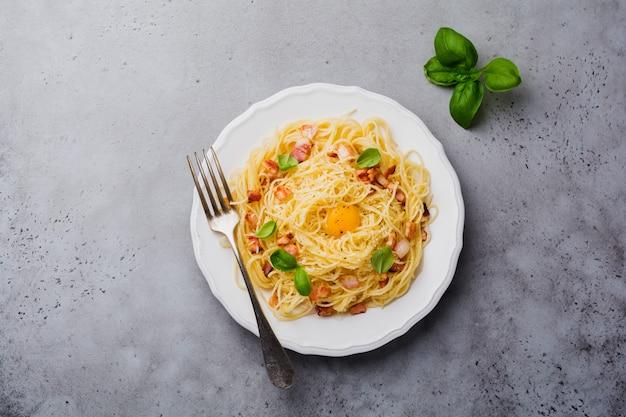 Pasta spaghetti carbonara mit speck, parmesan, eigelb und basilikumblättern auf grauer heller oberfläche. traditionelles italienisches gericht