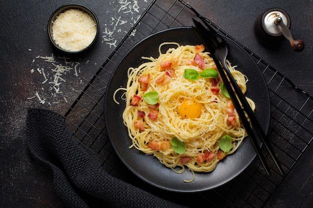 Pasta spaghetti carbonara mit speck, parmesan, eigelb und basilikumblättern auf schwarzer oberfläche. traditionelles italienisches gericht