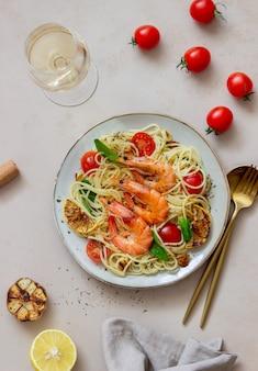 Pasta spaghetti mit garnelen, tomaten, knoblauch, spinat und zitrone. italienische küche. meeresfrüchte. diät.