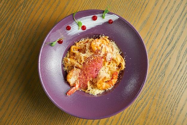 Pasta spaghetti mit garnelen und parmesan. nudeln mit meeresfrüchten in einer violetten schüssel gegen eine holzoberfläche. italienische küche