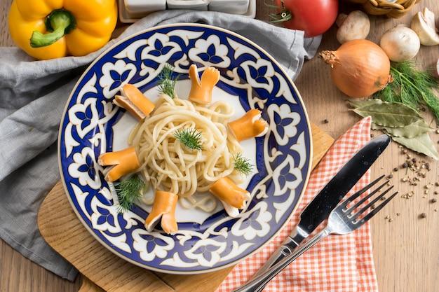 Pasta spaghetti mit salzwürsten und dill in einem teller mit einem traditionellen usbeken