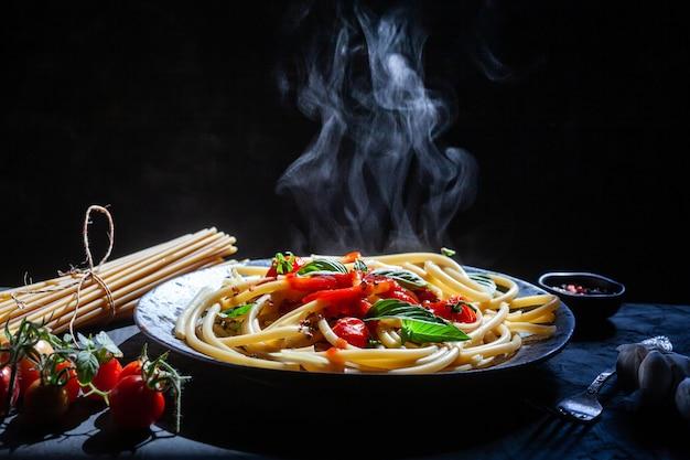 Pasta, spaghetti mit tomatensauce in schwarzer schüssel.