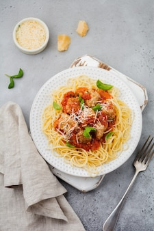 Pasta spaghetti mit tomatensauce, parmesan, basilikum und fleischbällchen auf weißer keramikplatte auf grauem beton oder steinhintergrund