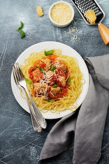 Pasta spaghetti mit tomatensauce, parmesan, basilikum und fleischbällchen auf weißer keramikplatte auf grauem beton