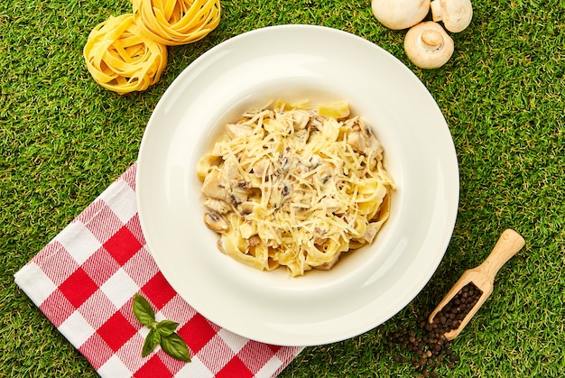 Pasta tagliatelle mit chiken, mashrooms und sahnesauce Premium Fotos