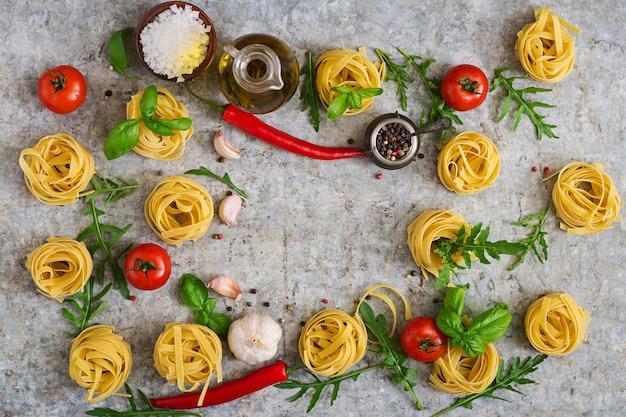 Pasta tagliatelle nest und zutaten zum kochen (tomaten, knoblauch, basilikum, chili). ansicht von oben