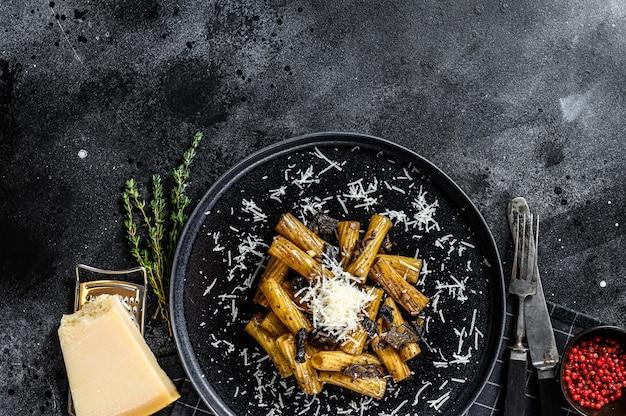 Pasta tortiglioni mit schwarzem trüffel, weißem pilz, sahnesauce und parmesan
