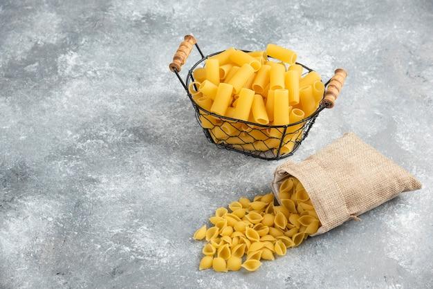 Pastasorten in einem metallischen korb und einer rustikalen tasche auf grauem tisch.
