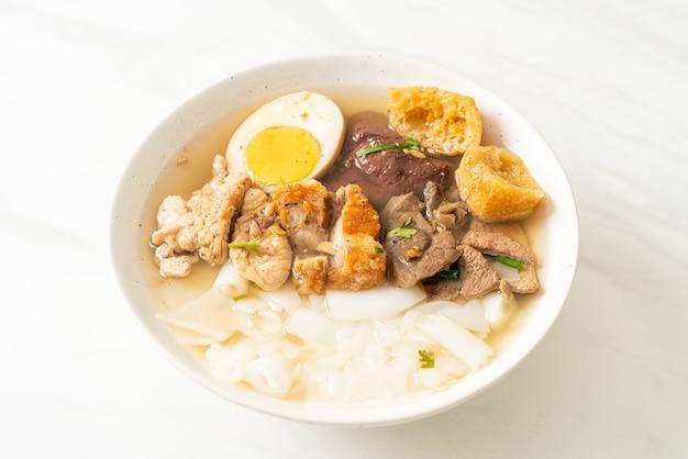Paste aus reismehl oder gekochtem chinesischem nudelquadrat mit schweinefleisch in klarer suppe - asiatische küche