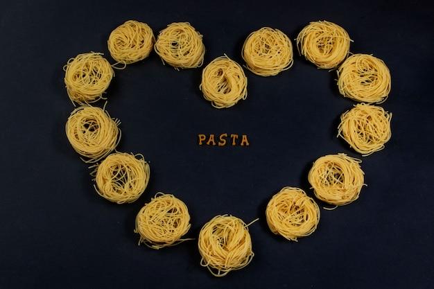 Paste der buchstaben des alphabets, auf einem schwarzen hintergrund mit einer herzform mit capelli-nudeln. in der mitte des herzens befindet sich eine inschrift - pasta