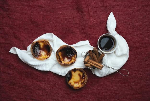 Pastel de nata. traditionelle portugiesische dessert-eierkuchen, tasse kaffee und zimtstangen im sieb auf der serviette über textilhintergrund. draufsicht