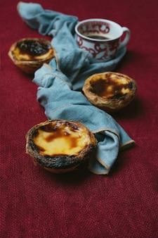 Pastel de nata. traditionelles portugiesisches dessert, eierkuchen und tasse kaffee über textilem hintergrund verziert mit serviette. selektiver fokus