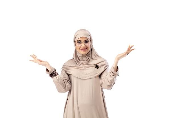 Pastell. schöne arabische frau, die im isolierten mode-, schönheits-, stilkonzept des stilvollen hijab aufwirft. weibliches model mit trendigem make-up, maniküre und accessoires.