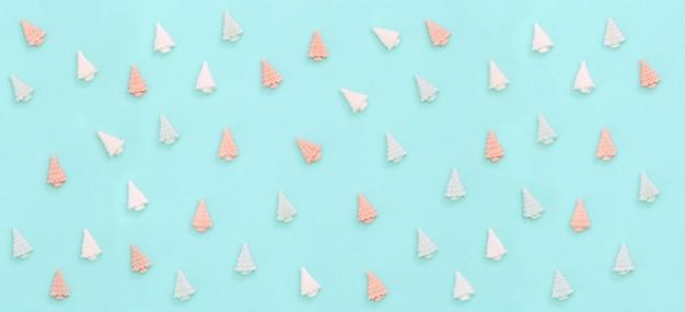 Pastell süße pralinen süßigkeiten in form von weihnachtsbäumen banner mit neujahrsmuster