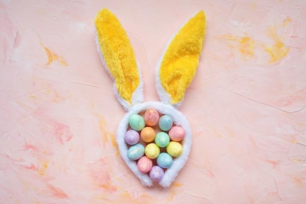 Pastell- und goldfarbene eier und hasenohren-osterfeierkonzept. draufsicht, flache lage, kopierraum