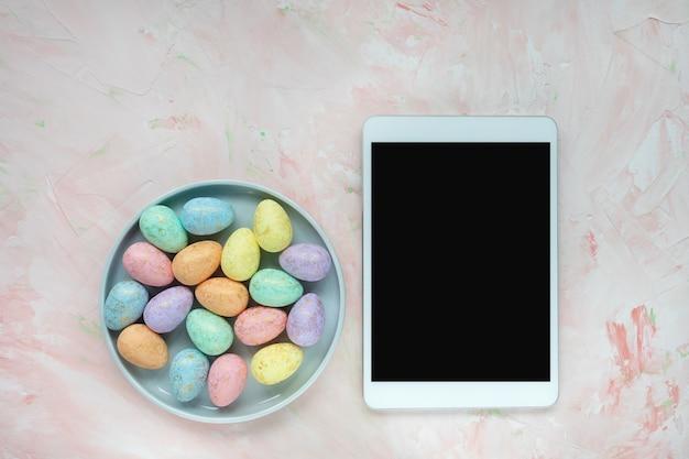 Pastell- und goldfarbene eierdekoration auf platte und tablet-computer auf rosa hintergrund. osterfestkonzept. draufsicht, flach liegen, verspotten