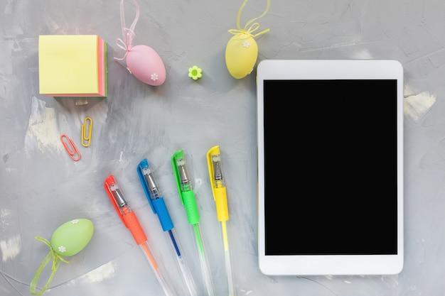 Pastell- und goldfarbene eierdekoration, stift, notizblock und tablette auf. osterfestkonzept. draufsicht, flach liegen, verspotten