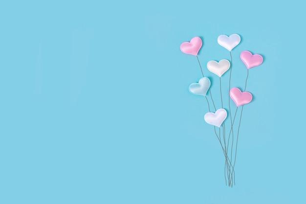 Pastellballons in der form des herzens auf blauem hintergrund. romantische grußkarte