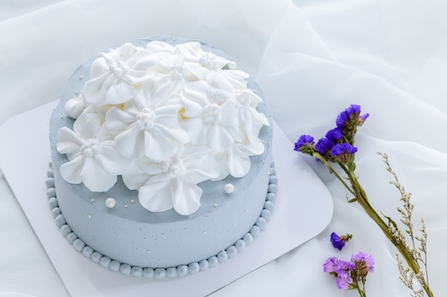 Pastellblauer kokosnusskuchen, verziert mit weißen blumen aus frischer sahne auf weißem stoff. hausgemachtes und minimales kuchenkonzept
