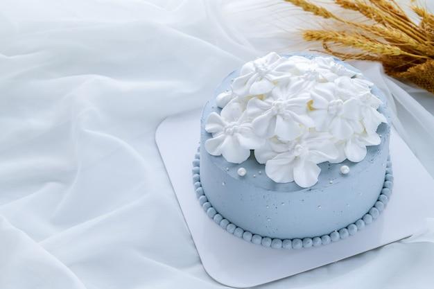 Pastellblauer kokosnusskuchen, verziert mit weißen blumen aus frischer sahne auf weißem stoff