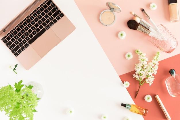 Pastellbürotischschreibtisch mit luftlaptop, blättern, frühlingsblumen, klemmbrett und kosmetischem zubehör der schönheit, draufsicht