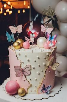 Pastellfarben leckeren kuchen mit schmetterling. weißer, gelber, rosa und blauer cremepudding