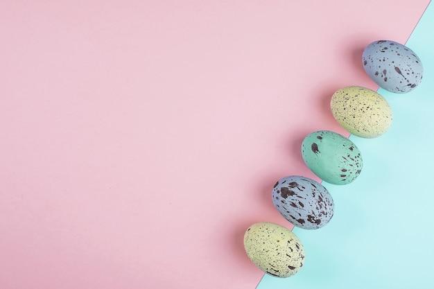 Pastellfarbene bunte ostereier auf trendigem papierhintergrund. flache lage, draufsicht, kopierraum