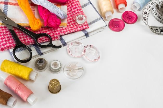 Pastellfarbener hintergrund, schneider- und designerschreibtisch, handcraft-zubehör, garnrolle, schere